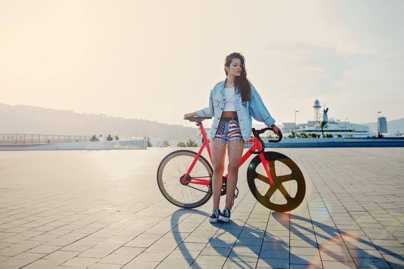 Mulher de cabelo marrom nova que está com sua bicicleta cor-de-rosa moderna no por do sol imagem de stock royalty free