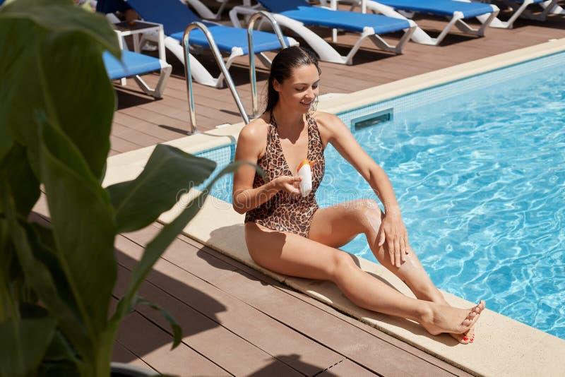 Mulher de cabelo preta adorável magnética que refrigera perto da piscina com cabelo molhado após nadar, guardando o recipiente co fotografia de stock