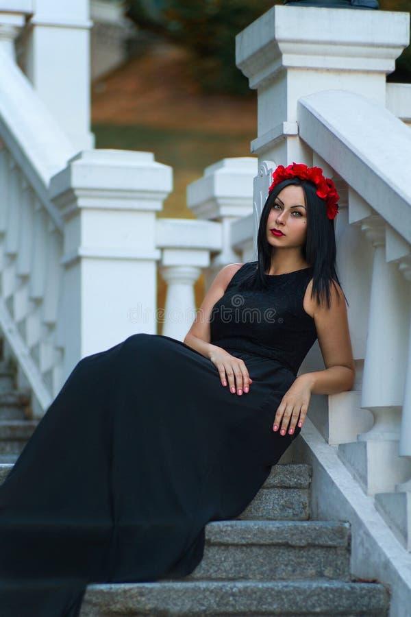 A mulher de cabelo preta no vestido escuro está esperando fotografia de stock royalty free