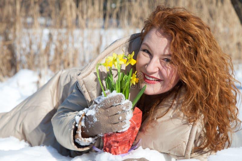 Mulher de cabelo vermelha alegre que encontra-se na neve e que guarda snowdrops amarelos fotografia de stock royalty free