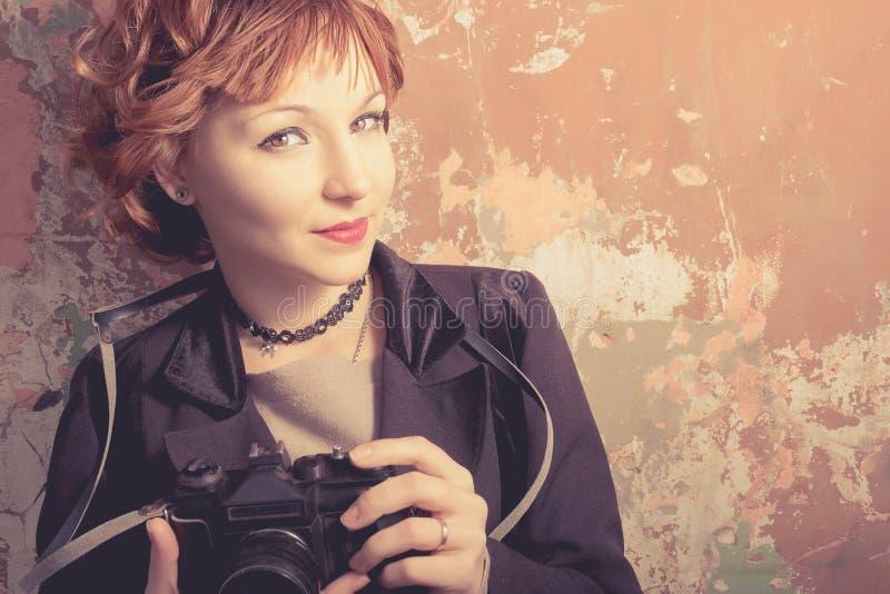 Mulher de cabelo vermelha do moderno que toma fotos com a câmera retro do filme fora imagem de stock royalty free