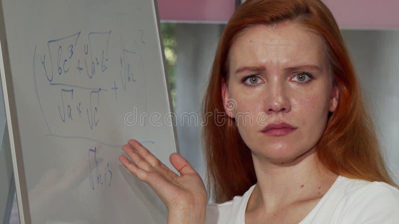 Mulher de cabelo vermelha nova que olha confundida ao resolver o problema de matemática fotos de stock