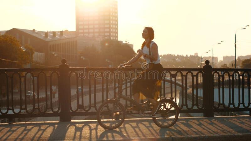Mulher de cabelo vermelha que monta uma bicicleta na luz solar do fundo na cidade imagem de stock royalty free