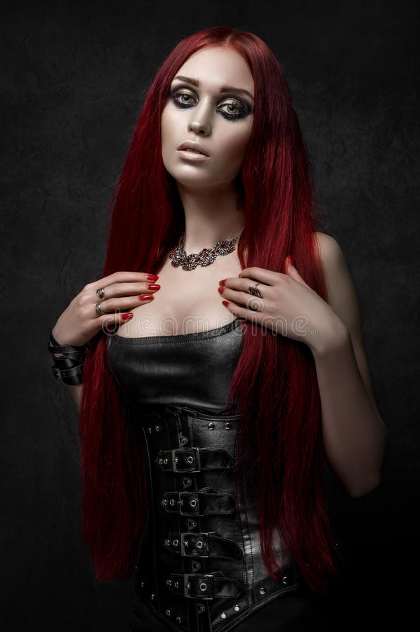 Mulher de cabelo vermelha 'sexy' na roupa de couro preta imagem de stock royalty free