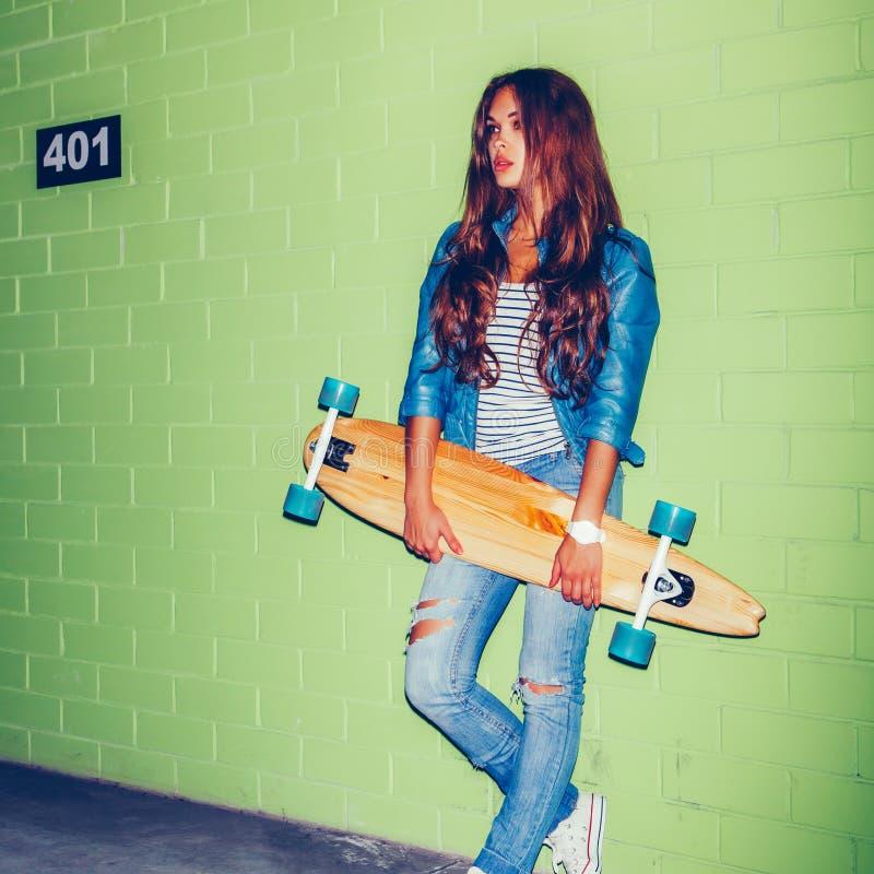 Mulher de cabelos compridos bonita com um skate longo de madeira perto da imagem de stock royalty free