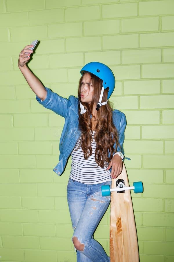 Mulher de cabelos compridos bonita com um smartpnone perto de um tijolo verde fotos de stock royalty free