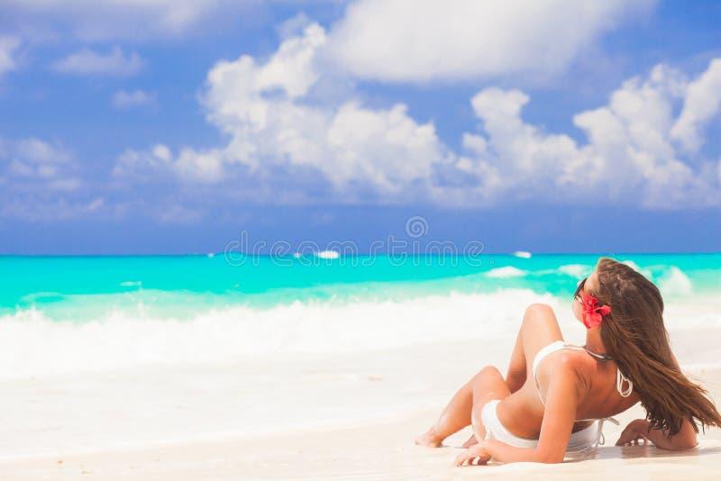 Mulher de cabelos compridos com a flor no cabelo no biquini na praia tropical foto de stock