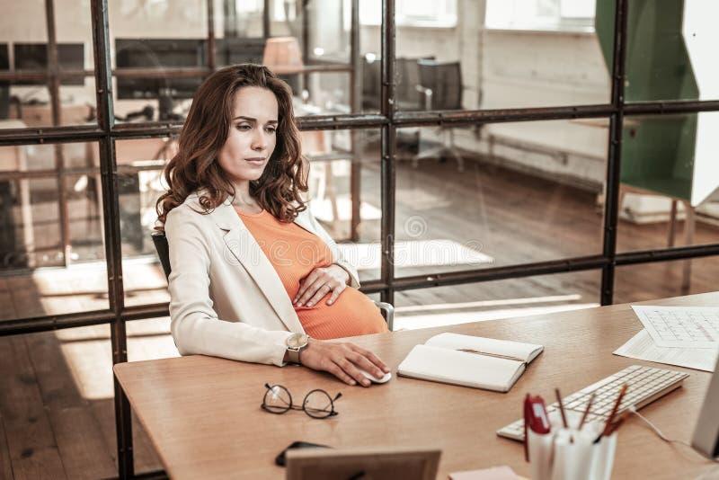 Mulher de cabelos compridos focalizada que mantém sua mão na barriga grávida foto de stock