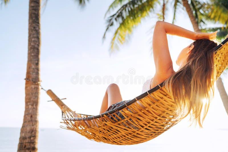 Mulher de cabelos compridos loura bonita nova que relaxa na rede sob palmeiras na praia da areia foto de stock