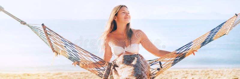 Mulher de cabelos compridos nova bonita que senta-se na rede no lado de mar imagens de stock