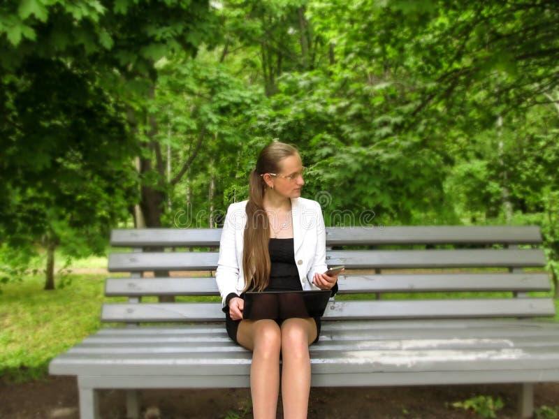A mulher de cabelos compridos nova com vidros guarda um telefone celular em sua mão e em um portátil em regaços e olha afastado,  foto de stock