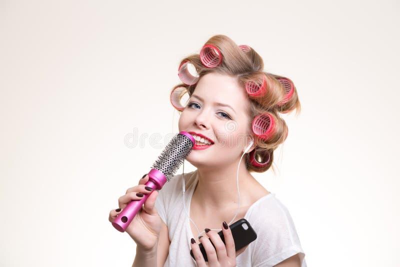 Mulher de canto com escova de cabelo e fones de ouvido imagens de stock