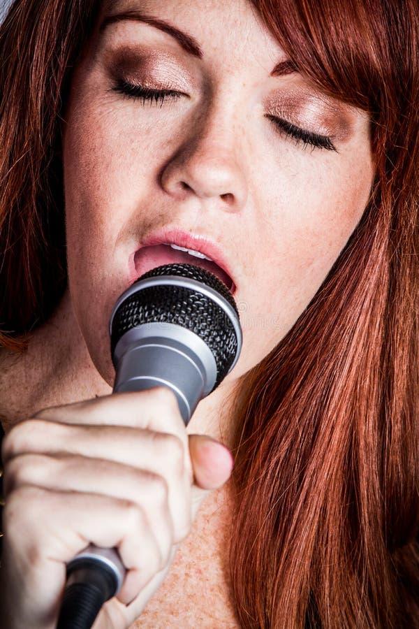 Mulher de canto do microfone fotografia de stock