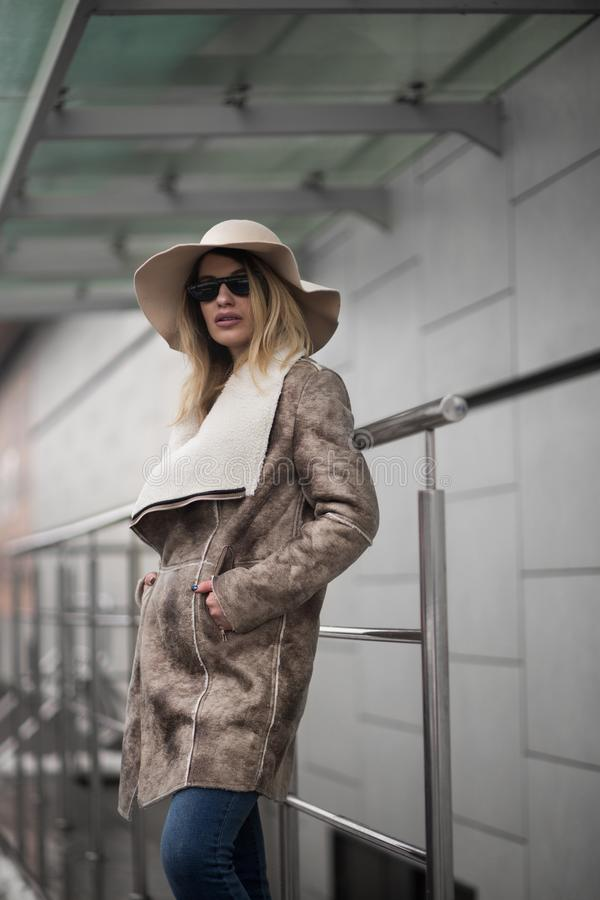 Mulher de casaco de suede castanho e chapéu de sol imagens de stock