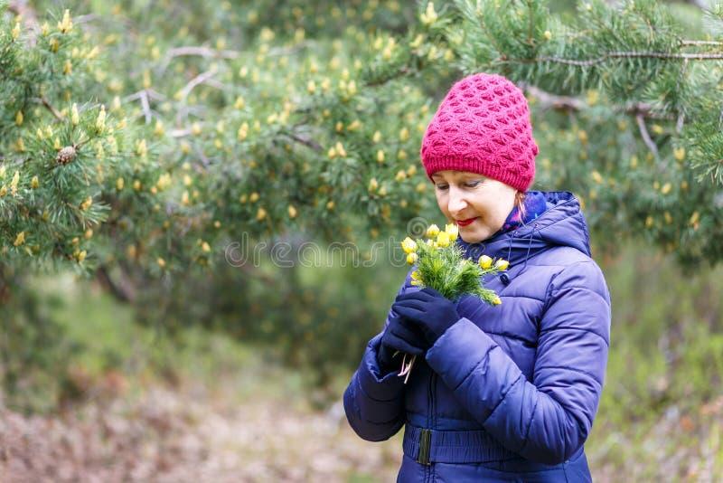 A mulher de cinquenta anos em um revestimento e em um chapéu da pena aspira flores amarelas fotografia de stock