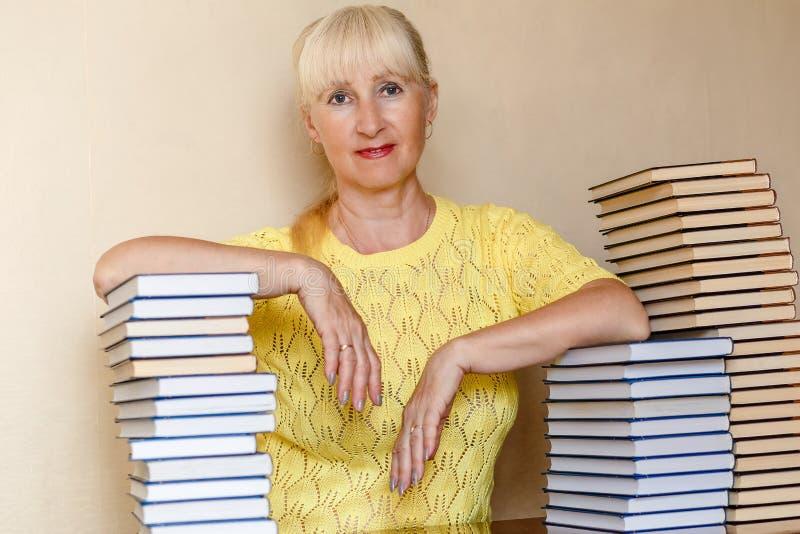 Mulher de cinquenta anos em uma camiseta amarela que senta-se em uma tabela com livros fotos de stock
