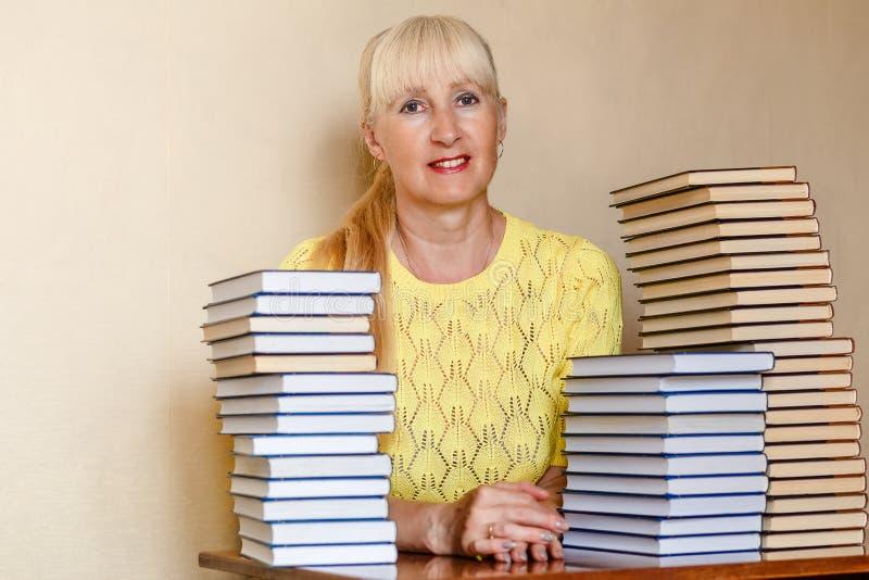 Mulher de cinquenta anos de sorriso em uma camiseta amarela que senta-se em uma tabela com livros foto de stock