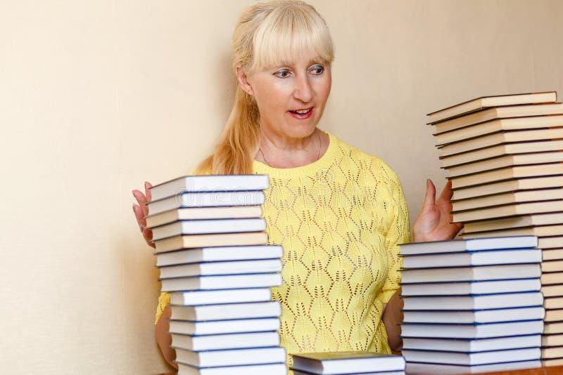 Mulher de cinquenta anos surpreendida em uma camiseta amarela e em muitos livros imagens de stock