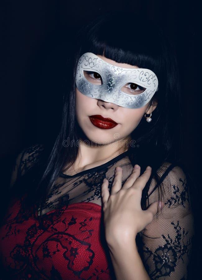 Mulher de comemoração nova em um vestido vermelho, máscara do carnaval em sua cara fotografia de stock royalty free