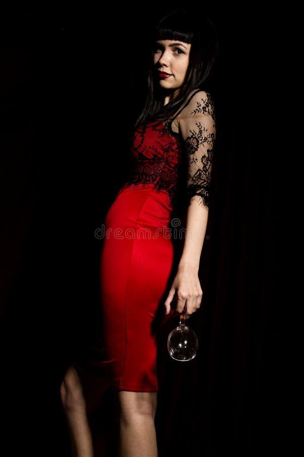Mulher de comemoração nova em um vestido vermelho que guarda um vidro que sai da escuridão imagem de stock royalty free