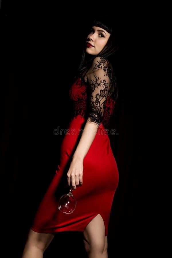 Mulher de comemoração nova em um vestido vermelho que guarda um vidro que sai da escuridão imagem de stock