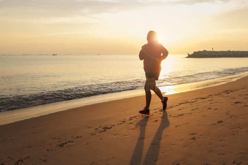 Mulher de corrida saudável do corredor durante o por do sol no movimento do exercício da praia o sunflare através da névoa dá a s imagem de stock