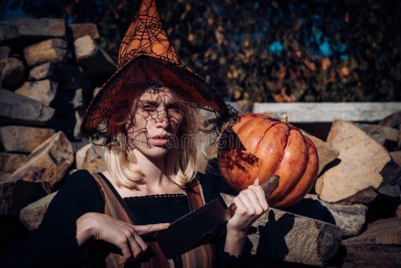 Mulher de Dia das Bruxas Menina ensanguentado assustador no chapéu alaranjado do feiticeiro com abóbora Mulher com sangue vermelh imagens de stock