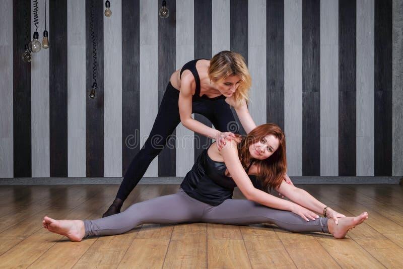 Mulher de dois esportes Instrutor da aptidão Lição com um instrutor Duas mulheres que fazem o esticão de volta à ajuda terminam imagens de stock royalty free