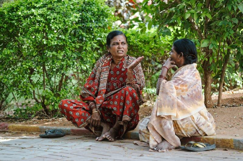 A mulher de dois indianos senta-se na terra e no discurso 8 de fevereiro de 2018 Sai Baba Ashram Puttaparthi imagens de stock royalty free