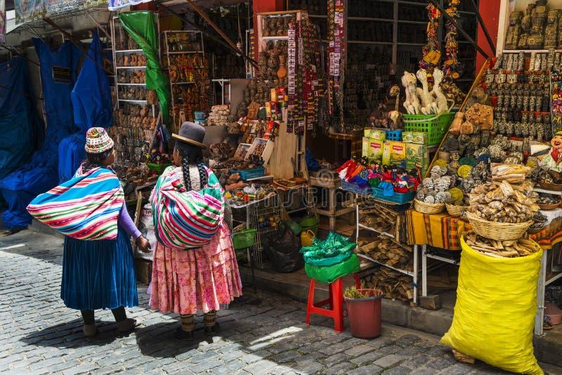 Mulher de dois local que veste a roupa tradicional na frente de uma loja em uma rua da cidade de La Paz, em Bolívia imagens de stock royalty free