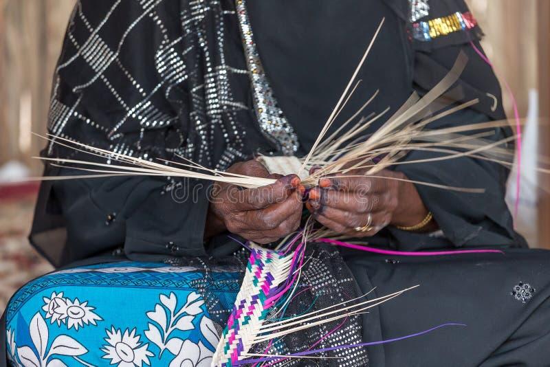 A mulher de Emirati está tecendo a cesta tradicional das folhas de palmeira, velocidade do obturador lenta para mostrar o movimen fotos de stock