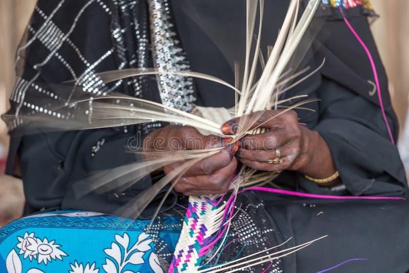 A mulher de Emirati está tecendo a cesta tradicional das folhas de palmeira, velocidade do obturador lenta para mostrar o movimen imagens de stock