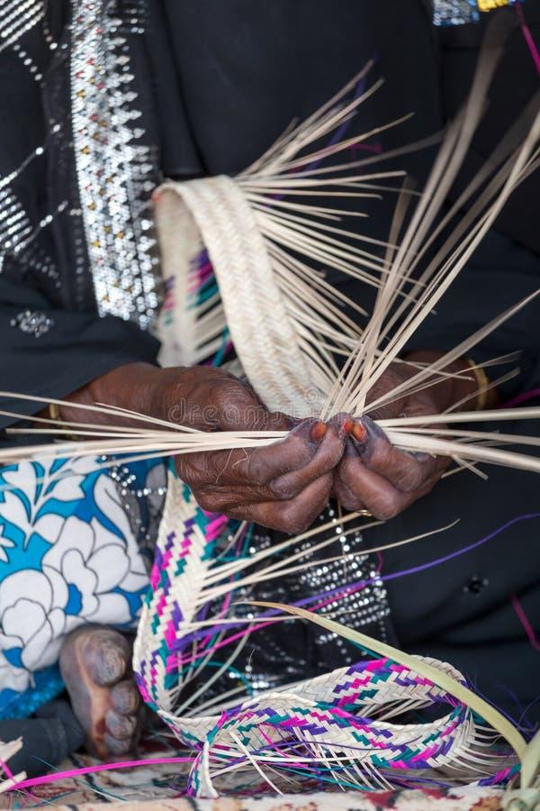 A mulher de Emirati está tecendo a cesta tradicional das folhas de palmeira, velocidade do obturador lenta para mostrar o movimen fotografia de stock royalty free