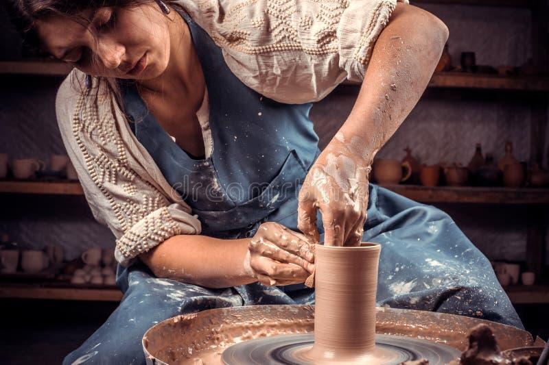 A mulher de encantamento do ceramist mostra como trabalhar com a roda da argila e da cerâmica Fazendo pratos cer?micos fotos de stock royalty free