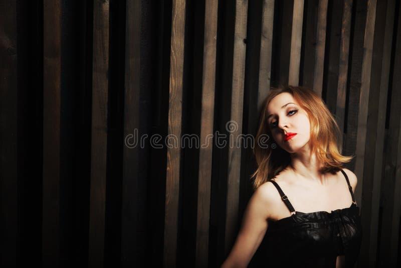 Mulher de encontro a uma parede de madeira foto de stock royalty free