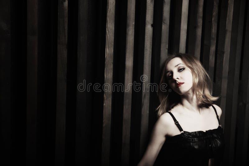 Mulher de encontro a uma parede de madeira imagem de stock