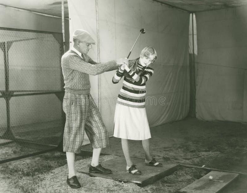 Mulher de ensino do instrutor para jogar o golfe fotografia de stock royalty free