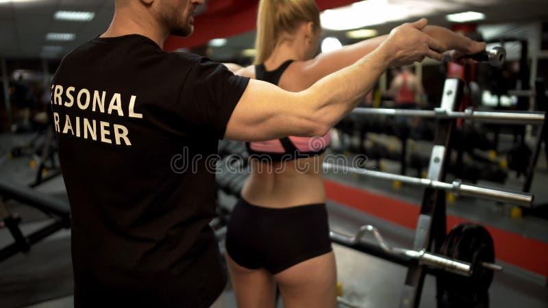 Mulher de ensino do instrutor para levantar o gym dos pesos, programa de formação pessoal, esporte fotografia de stock royalty free