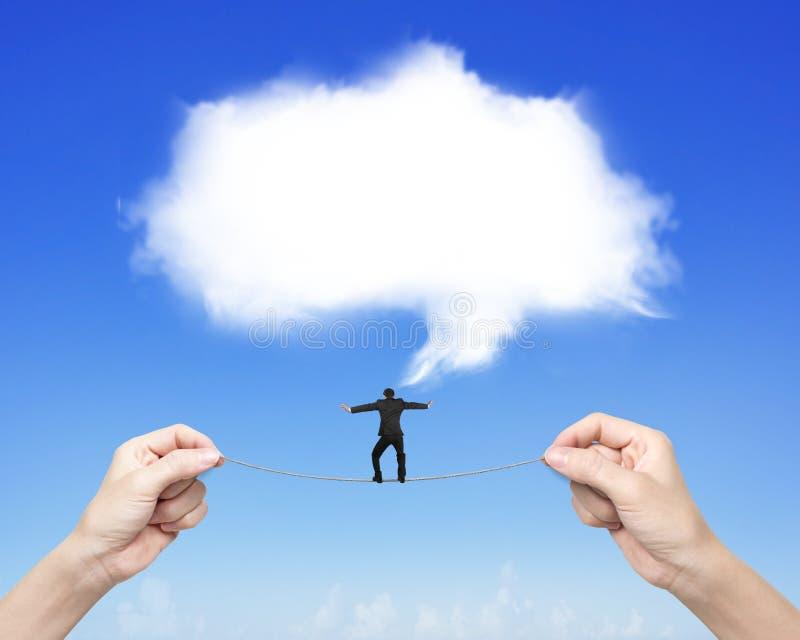 A mulher de equilíbrio da corda-bamba do homem de negócios entrega guardar a nuvem branca fotografia de stock