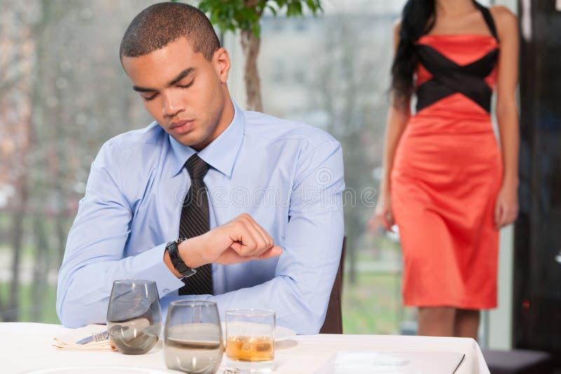 Mulher de espera do homem considerável e vista do relógio foto de stock royalty free
