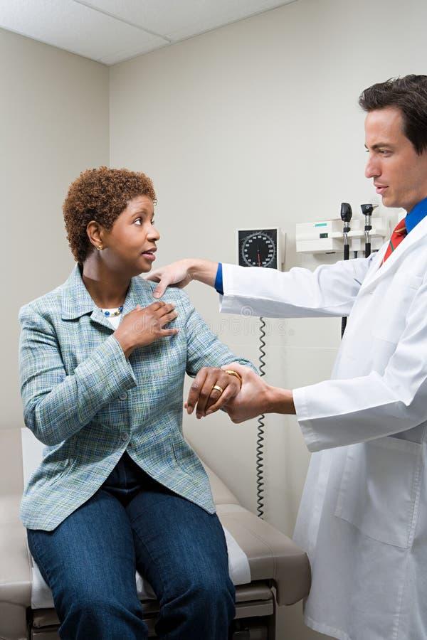 Mulher de exame do doutor fotografia de stock