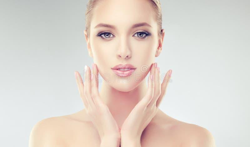 A mulher de fascínio com pele fresca limpa está tocando na cara maciamente foto de stock