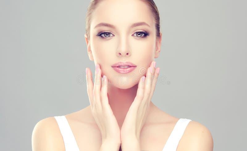 A mulher de fascínio com pele fresca limpa está tocando na cara maciamente fotografia de stock