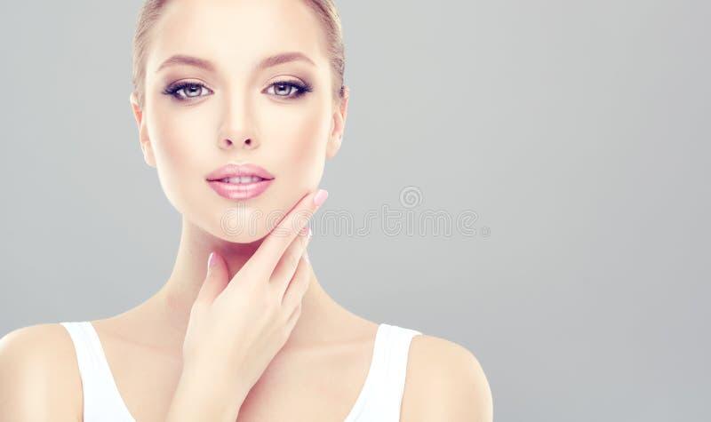 A mulher de fascínio com pele fresca limpa está tocando na cara maciamente imagens de stock