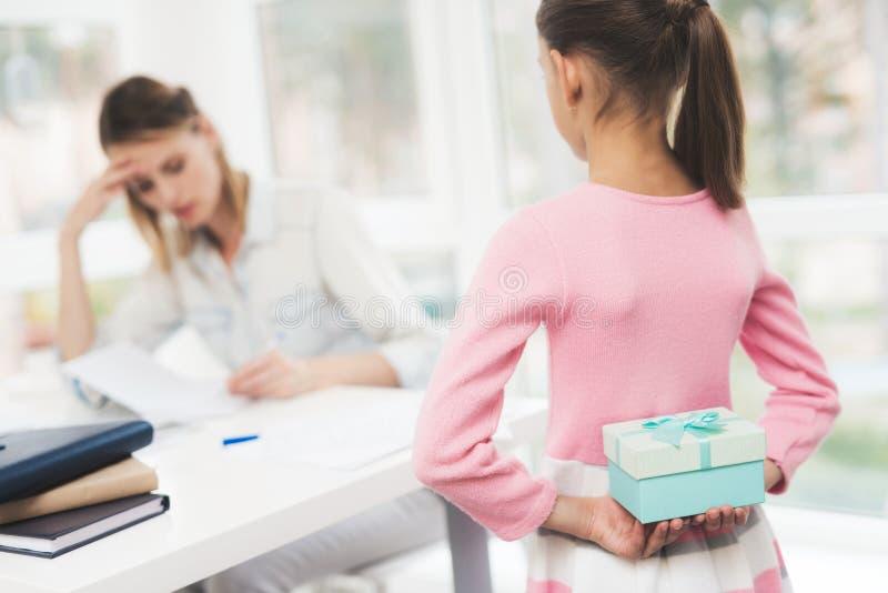 Mulher de funcionamento em licenças de parto A filha fez um presente para sua mãe amado imagem de stock royalty free