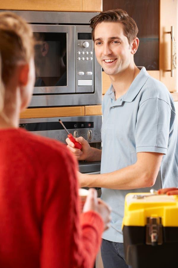Mulher de Giving Advice To do coordenador no reparo do fogão foto de stock