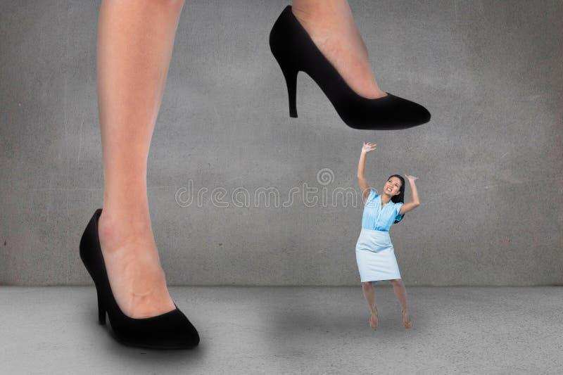 Mulher de grande negócio que tenta pisar em uma mulher da empresa de pequeno porte fotos de stock royalty free