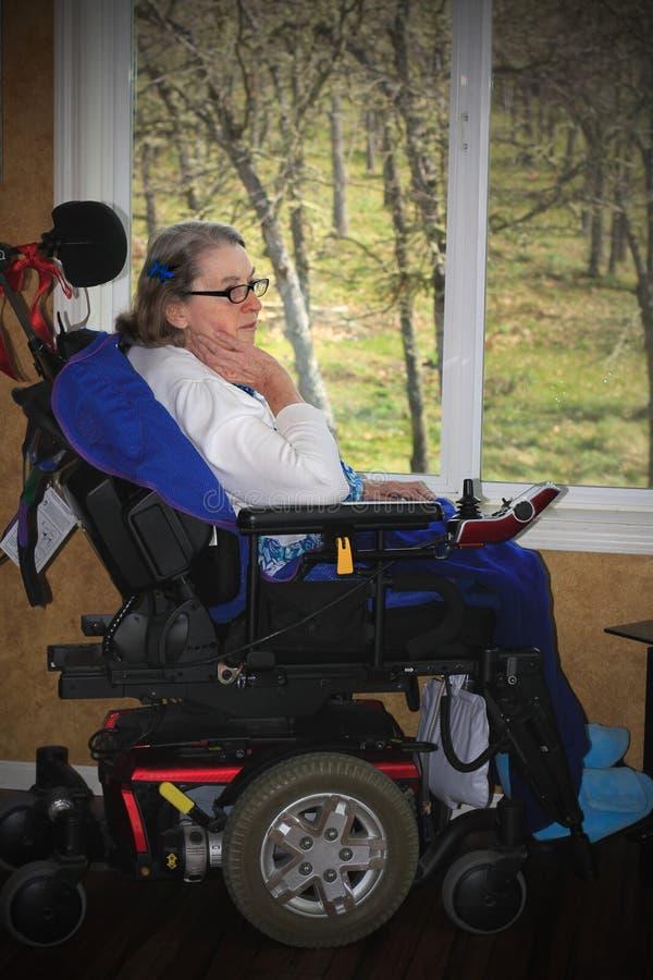 Mulher de Handycapped que senta-se pela janela imagem de stock