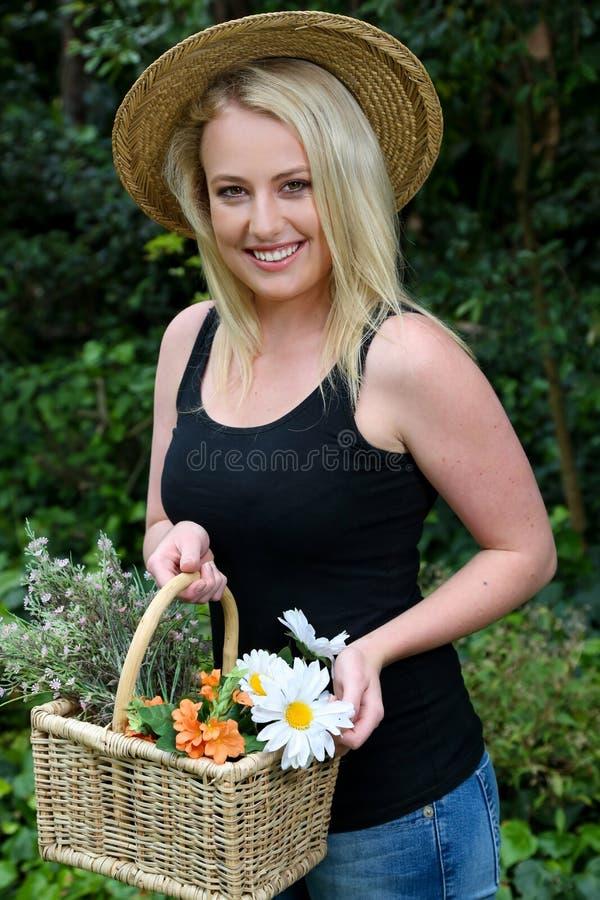 Mulher de jardinagem bonita com flores fotos de stock royalty free
