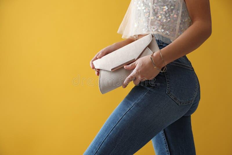 Mulher de jeans com bolsa de embreagem no fundo, vestida foto de stock royalty free